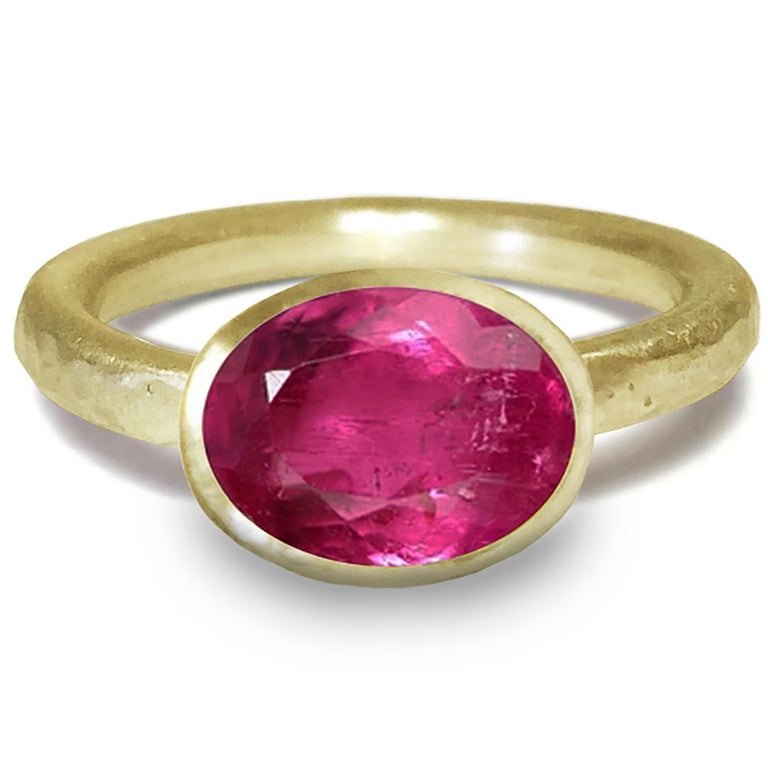 18 Karat Yellow Gold Ring by Deborah Murdoch is from the Abundance Collection featuring an oval Pink Tourmaline Stone. The ring band is slightly planished giving that textural feel and has a silky satin finish.   Metal: 18 Karat Yellow Gold / This