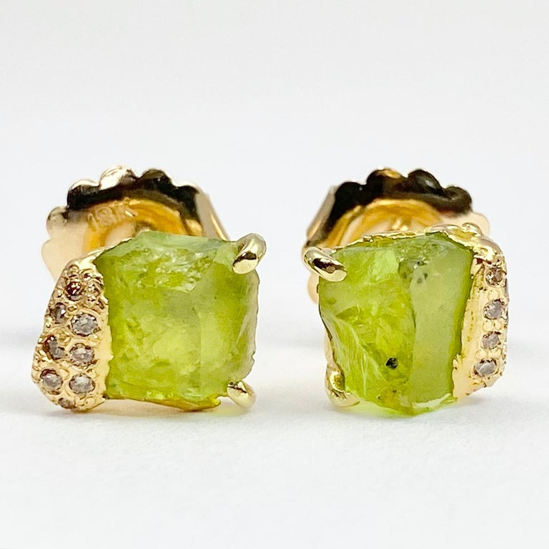 Pair of Pia stud earrings, from the Watu Collection, in 18 karat recycled yellow gold. Earrings feature two untreated, Tenda cut peridot weighing approximately 3.44 carats; and 16 round natural color accent diamonds, totaling approximately 0.11