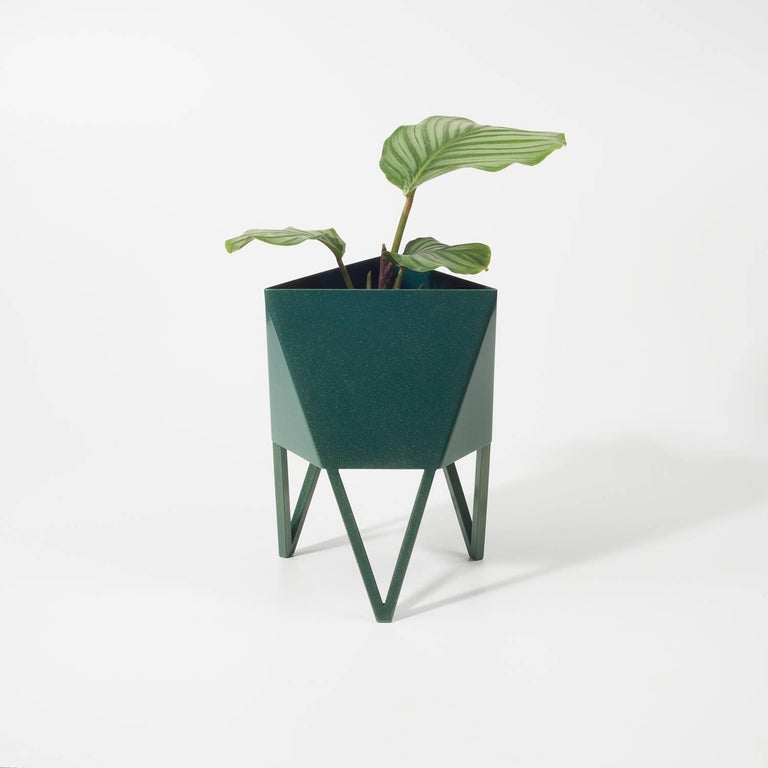 Introducing Force/Collide's signature planter in sunbeam blue green. Using a seamless brake-forming technique, one sheet of steel is wrapped into a unique geometric pattern that's triangular at the top and hexagonal at the base. Three V-shaped legs