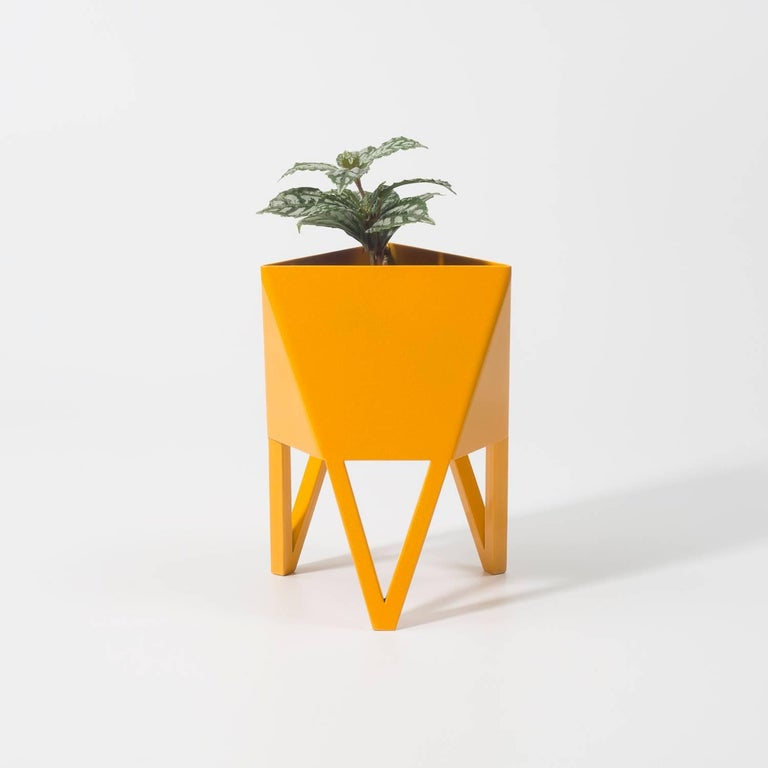 Introducing Force/Collide's signature planter in sunbeam daffodil yellow. Using a seamless brake-forming technique, one sheet of steel is wrapped into a unique geometric pattern that's triangular at the top and hexagonal at the base. Three V-shaped