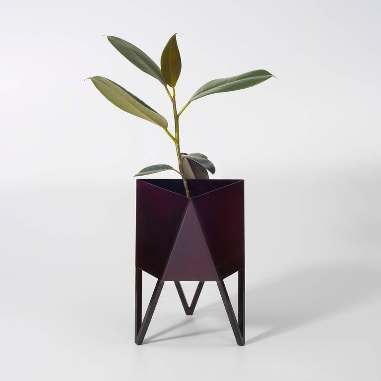 Introducing force/Collide's signature planter in glossy maroon. Using a seamless brake-forming technique, one sheet of steel is wrapped into a unique geometric pattern that's triangular at the top and hexagonal at the base. Three V-shaped legs