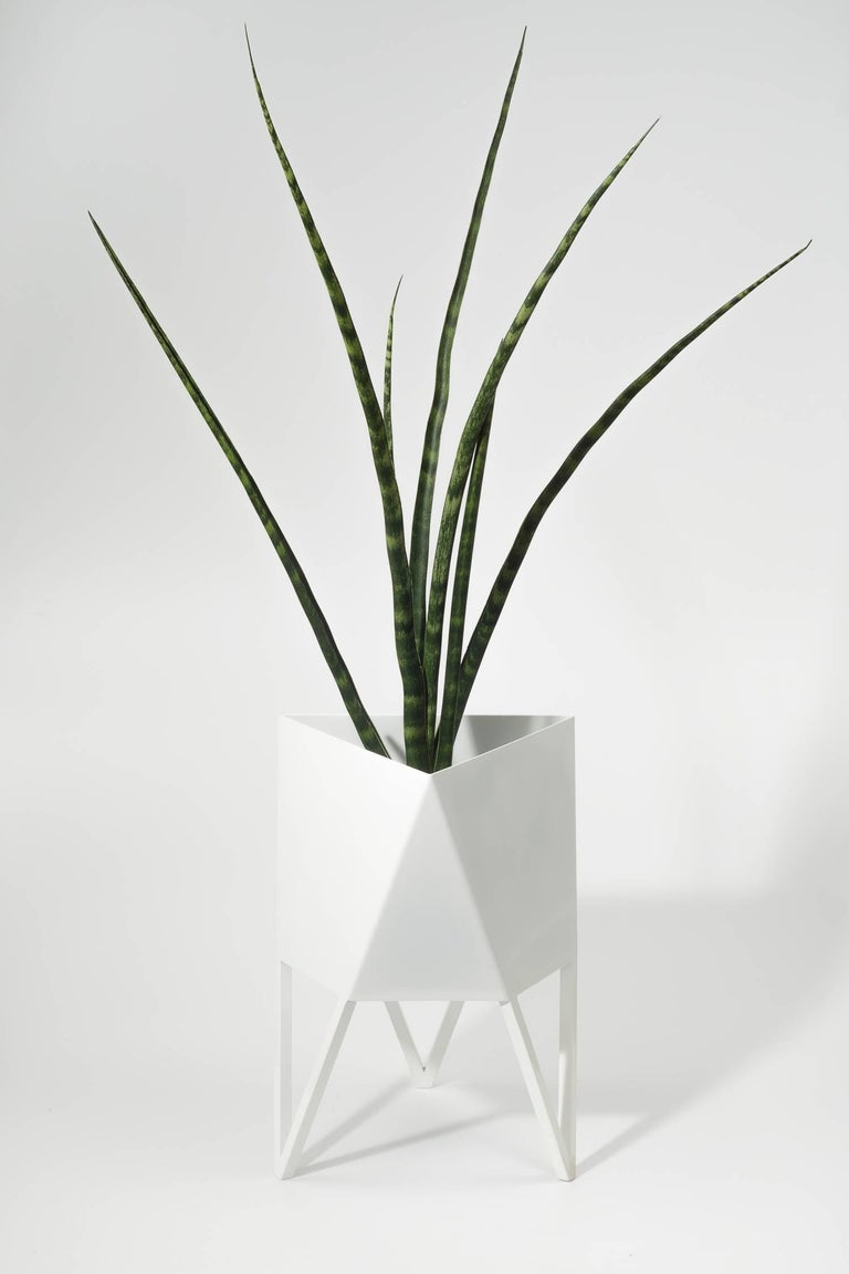 Introducing force/Collide's signature planter in glossy white. Using a seamless brake-forming technique, one sheet of steel is wrapped into a unique geometric pattern that's triangular at the top and hexagonal at the base. Three V-shaped legs