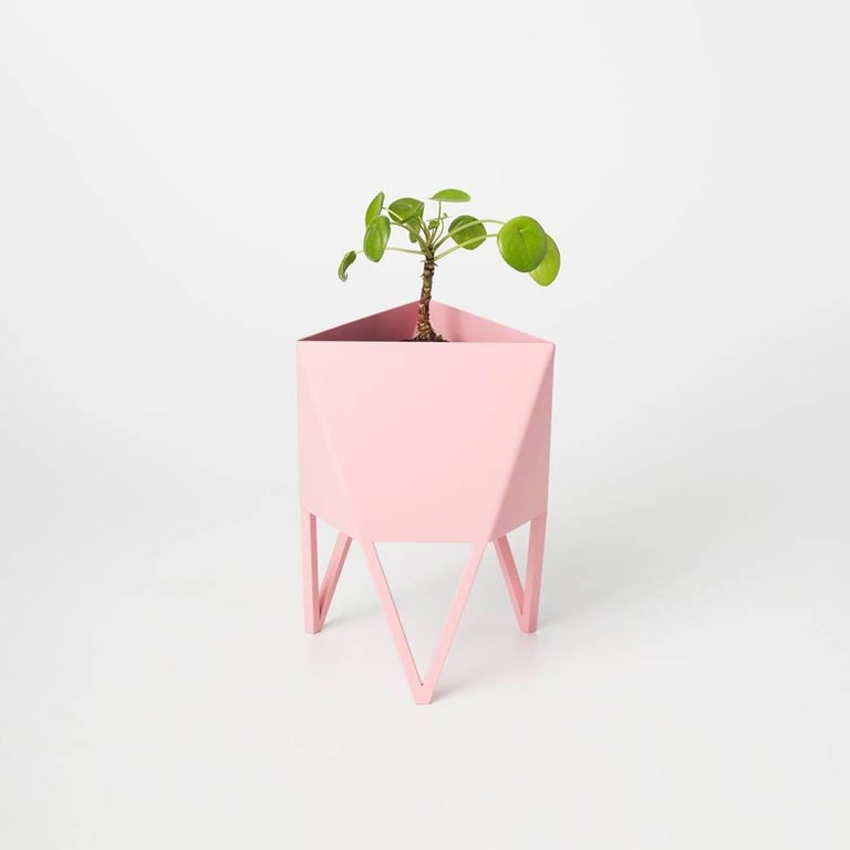 Introducing Force/Collide's signature planter in flat light pink. Using a seamless brake-forming technique, one sheet of steel is wrapped into a unique geometric pattern that's triangular at the top and hexagonal at the base. Three V-shaped legs