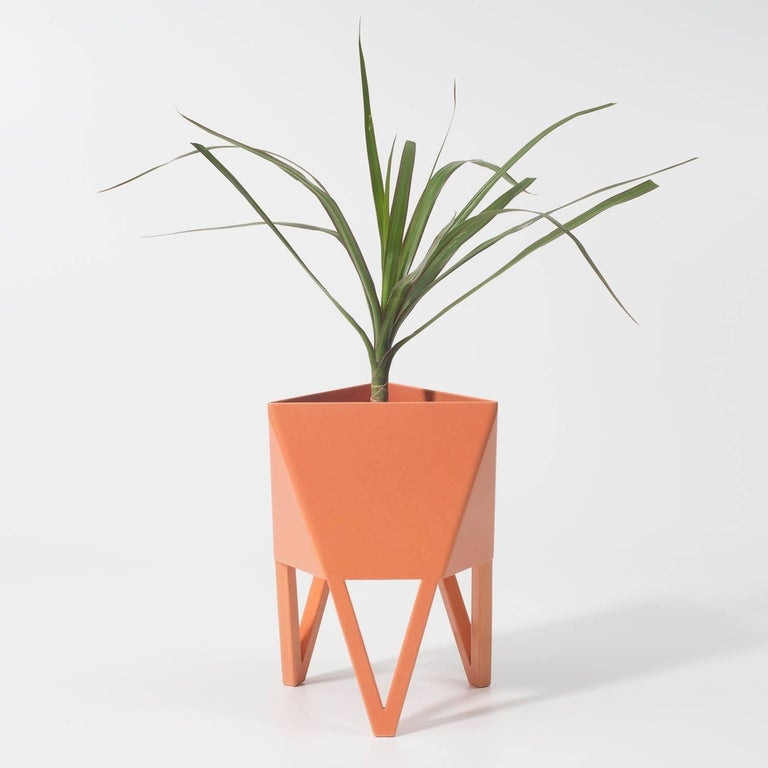 Introducing Force/Collide's signature planter in Sunbeam salmon pink. Using a seamless brake-forming technique, one sheet of steel is wrapped into a unique geometric pattern that's triangular at the top and hexagonal at the base. Three V-shaped legs