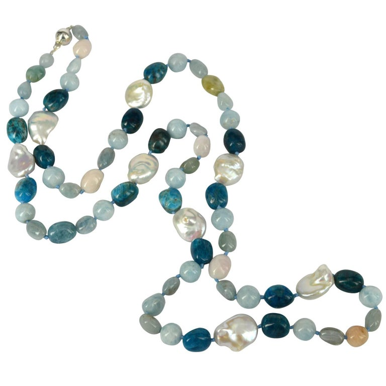 Beautiful Shades of Blue with a hint of pink make this lovely long necklace. 12mm Polished Aquamarine, approx 14mm Beryl  (multi-Colour Aquamarine and Morganite) nuggets, 16x12mm Bright blue apatite and 21mm plus Baroque Fresh Water Coin Pearls with
