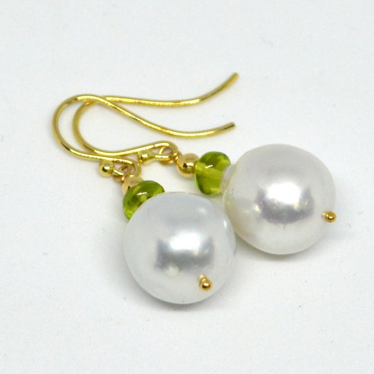 Natural Polished Peridot 5x3mm with 15x12.8mm high sheen South Sea Pearls set on 9ct yellow Gold Sheppard,  14k Gold head pin and 3mm round bead.  Total Earring length 36mm.