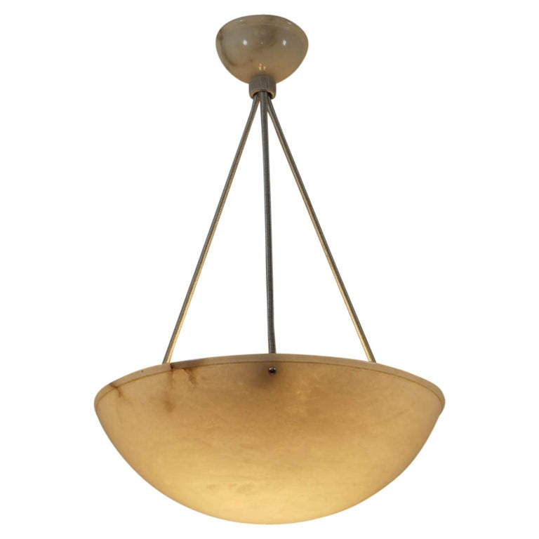 A highly mineralized alabaster shade has been carved into a bowl with rim shape and a matching ceiling canopy.