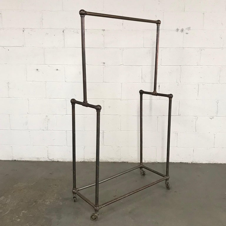 Deco era, rolling, department store, garment rack is nickel-plated, copper oxide (japanned), tubular iron. The bottom portion height is 39 inches.