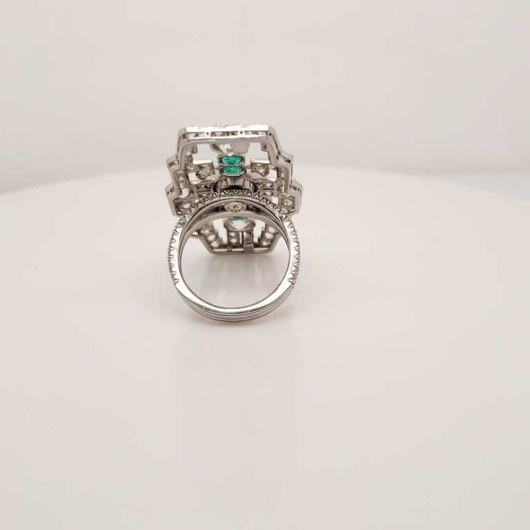 This large Diamond and Emerald Statement Ring contains a 1 GIA certified, Round Brilliant Cut, Fancy Deep Greenish Yellow diamond weighing 1.76 carats. It is mounted with four emeralds, and Old Mine Round diamonds weighing a total of 5.99 carats. It