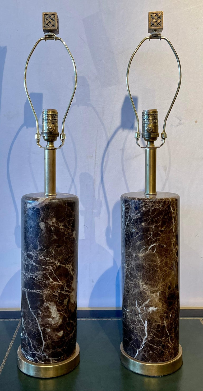 Pair of brass base marble cylindrical form table lamps with finials in the Art Deco fashion. Shades are not included.