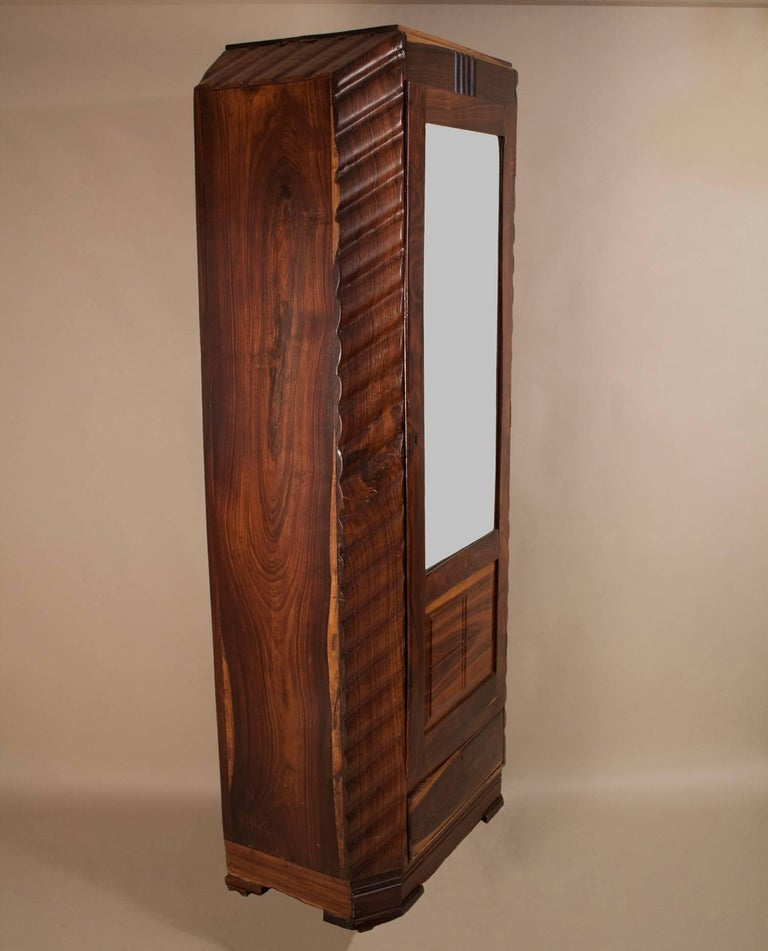 Tall, slender Art Deco wardrobe in rosewood with a rich grain and interesting tonal variations. The cabinet is carved with a consistent wave pattern and has a flattering 3/4-length mirror door with working lock and key. There are two drawers for