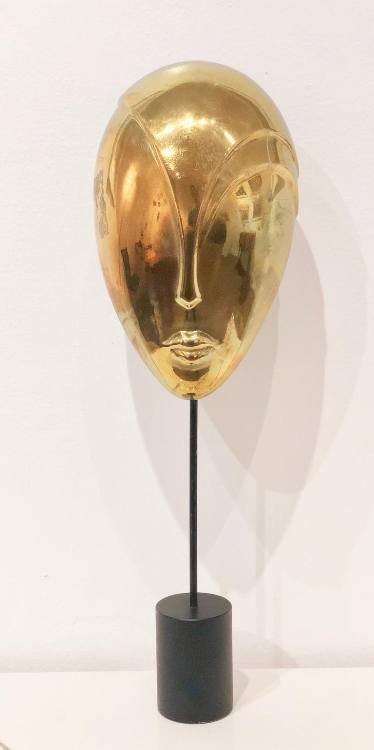 Unique solid brass decorative mask sculpture in polished brass finish with black enamel finish bases.