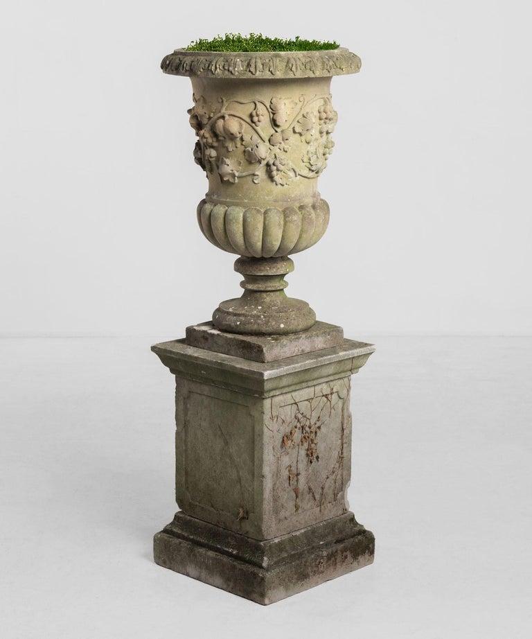 Decorative cast stone urn with pedestal, circa 1950.  Beautifully cast urn with decorative flower motif.
