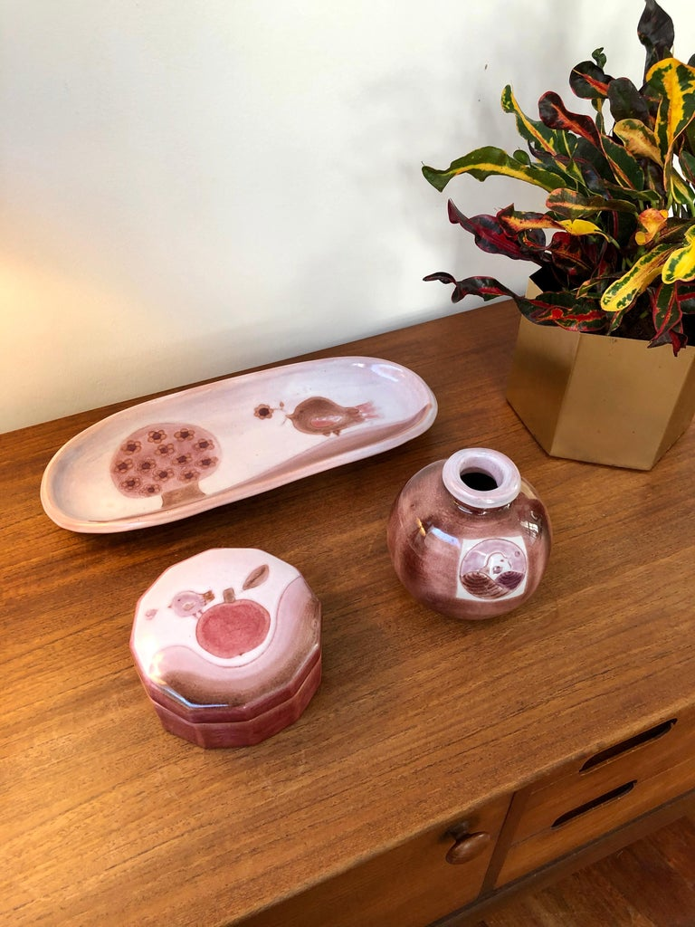 Decorative ceramic set including a tray, small vase and safe-keeping box by the Cloutier brothers (circa 1970s). All pieces made in one of the Cloutier's trademark pinkish-purple colours with whimsical designs with tree (décor arbre), birds and