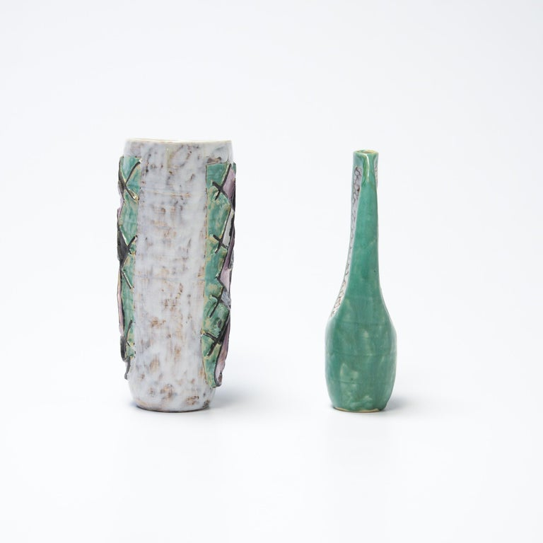 This decorative pair of ceramic vases are dated 1957. It is a nice set in mint green, light lilac, black and white. The vases are in very good condition. Both vases are marked.
