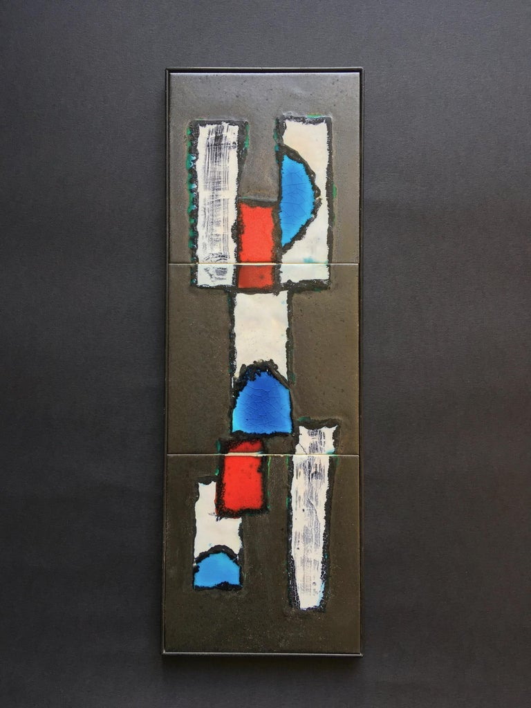 Decorative ceramic wall art with black metal frame, Belgium, mid-20th century.  Decorative wall art comprising three handmade ceramic panels with abstract design in white, red and strong blue/turquoise, in a combination of matte, gloss and