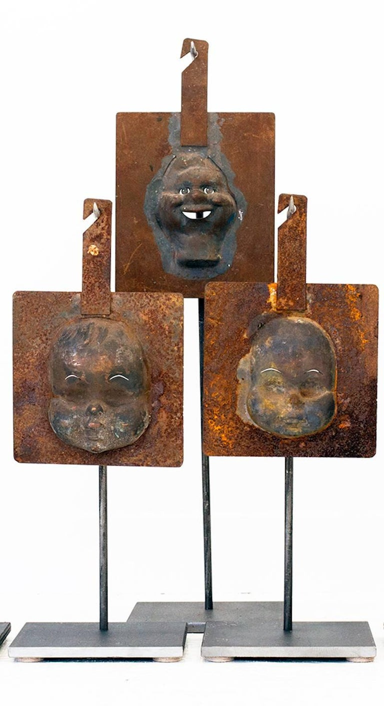 Collection of seven 1940s (six) doll head injection mold metal plates, including one (1) Howdy Doody collector's piece injection mold metal plate. A graphic table, bookcase or center table accessory with nice patina and custom handmade steel stands.