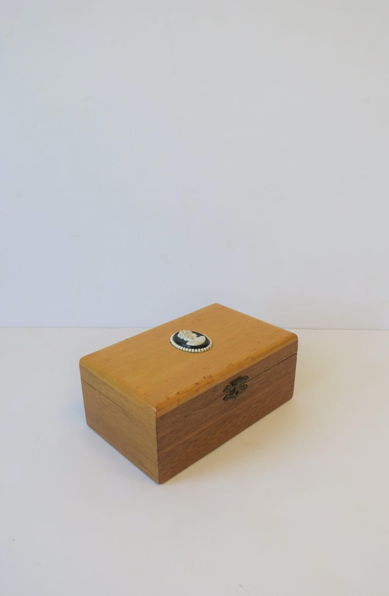 A beautiful blonde wood box with black and white Cameo design. Interior is cobalt blue velvet lined. Cameo is a resin or composite material. A great piece as decorative or to hold jewelry (as demonstrated) or other items on a desk, vanity,