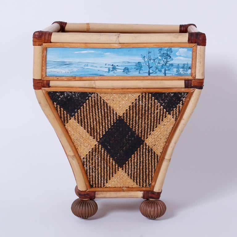 Well-dressed waste basket crafted with bamboo, wicker and reed. Featuring four monochrome landscapes with woven argyle side panels and beaded bun feet.