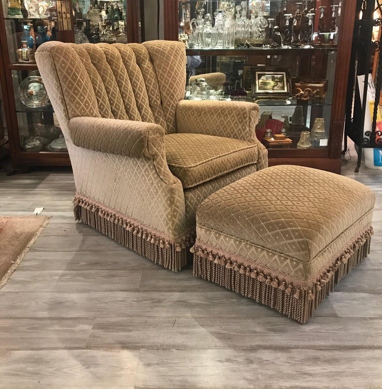 Stylish upholstered chair and ottoman in cut velvet with bouillon fringe. The chair with an 8 way hand tied spring construction and kiln dried hardwood frame made by Swaim. This Art Deco 1940s style the channeled back with a gentle cure for comfort.