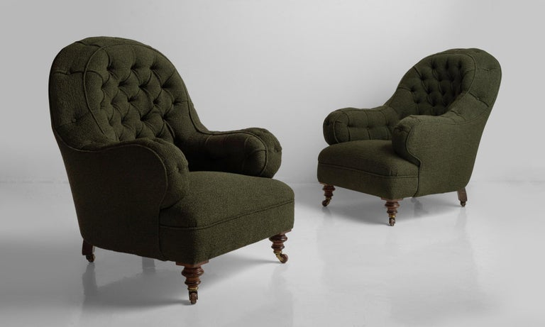 Deep buttoned armchairs, England, circa 1860.  Newly reupholstered with turned walnut front feet.