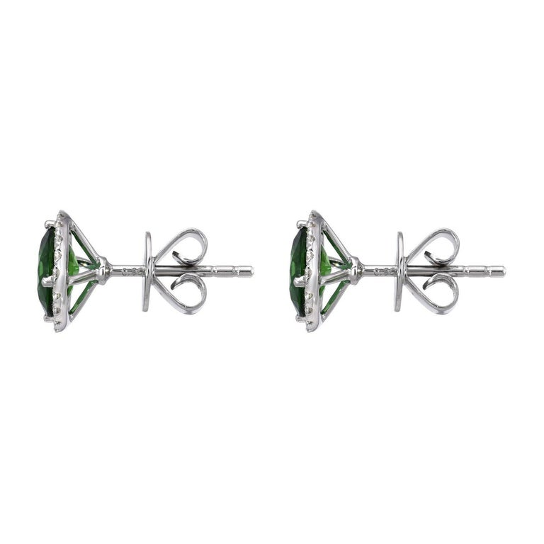 A pair of deep Chrome Green Tourmaline rounds, weighing a total of  1.96 carats, are surrounded by a a halo of round brilliant diamonds weighing a total of 0.25 carats, in these 18K white gold stud earrings for women. Returns are accepted and paid