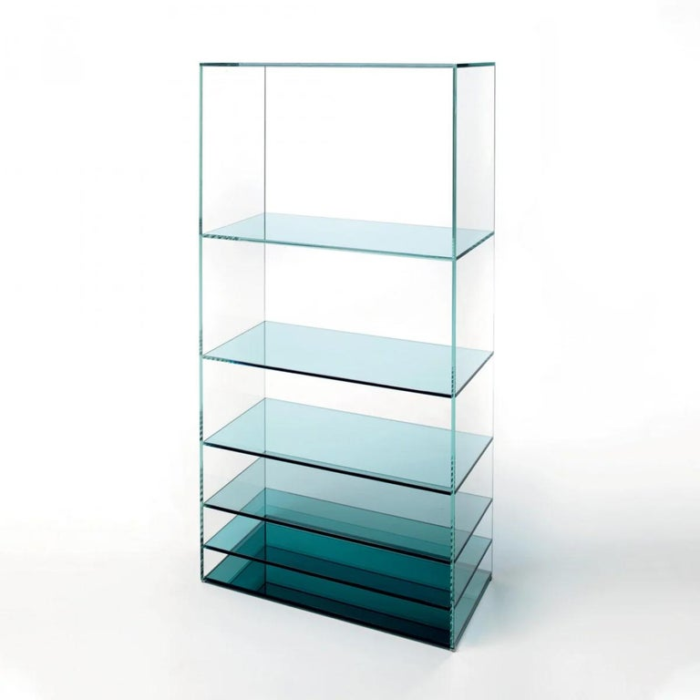 Deep Sea bookcase is shown here in the light blue transaprent glass shelves. Collection of bookcase in laminated and thermo-welded transparent extralight glass. The shelves of the bookcase and the vertical elements of the low tables are in colored