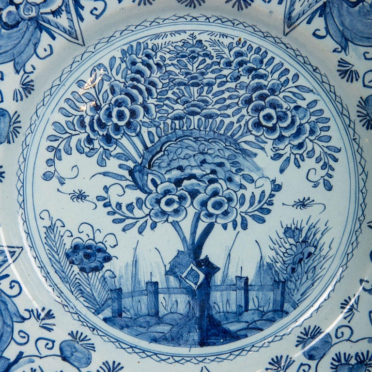 A Dutch delft blue and white charger hand painted showing a flowering tree in a fenced garden. Grasses, a single large flower, and insects are shown behind the fence. This design is contained within a circle formed by a chain of small crossed X's.