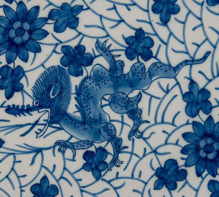 Blue and white dragon dish. Delft, 1722-1757  The Greek A pottery Mark: AIK, period J van der Kool (1722-1757) Dish with blue and white decoration of a dragon on a dense ground of flowers and foliage. The well is undecorated. The border is