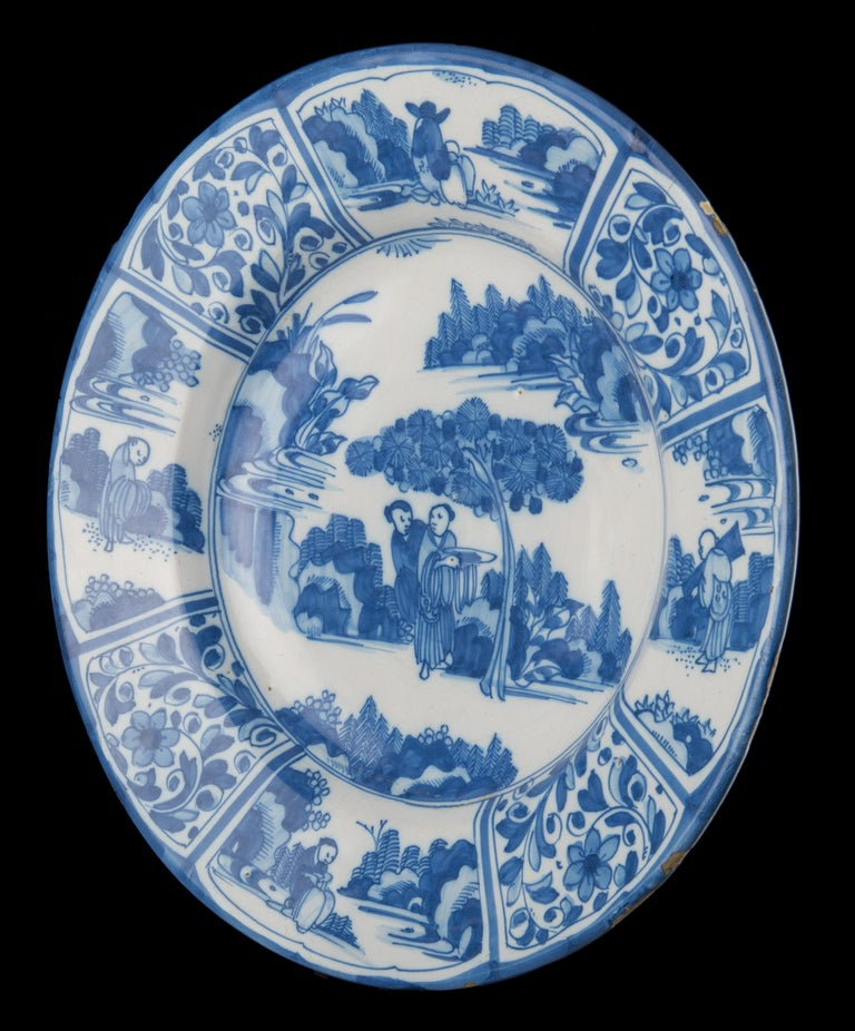 Blue and white chinoiserie dish. Delft, circa 1670   Blue and white dish with a wide-spreading flange, the center painted with two conversing Chinese under a tree in an oriental landscape. One man carries a dish. The eight-panelled border is