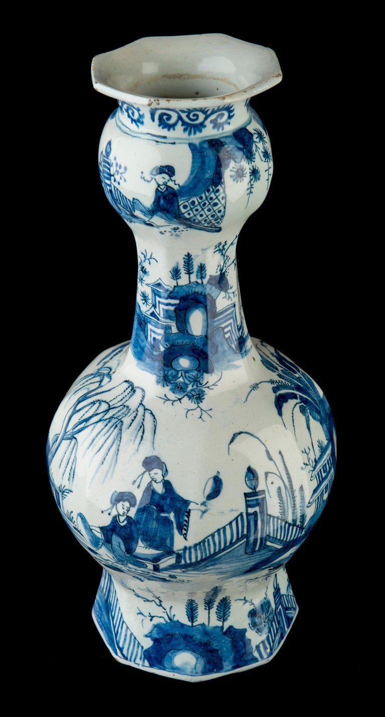 The octagonal bottle vases stand on a wide, spreading foot with a garlic neck over a spherical body ending in a trumpet-shaped mouth. The vases are painted with a continuous chinoiserie design. Around the foot, the body, the neck and the bulb four