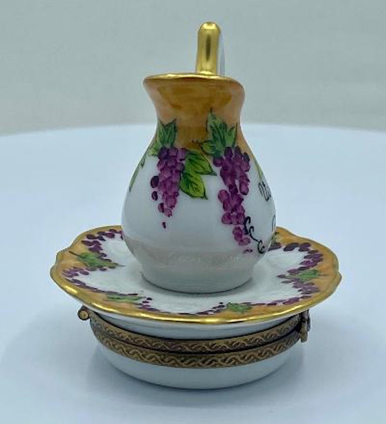 Collectible Limoges porcelain miniature trinket box is handmade and hand painted in France and features beautifully hand painted grapes and vines on the wine pitcher with an attached plate on the bottom of the box. Rich hand painted 24-karat gold