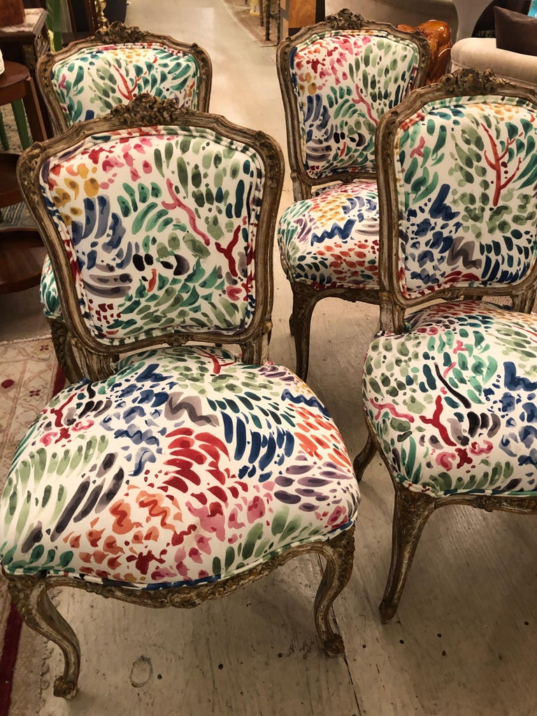 A chic adorable set of 4 Classic Louis XVI distressed painted carved wood side dining chairs, newly updated in a fun abstract pattern upholstery. Fabric has splashes of magenta, fushia, lime green and purple against a cream background. Wood has