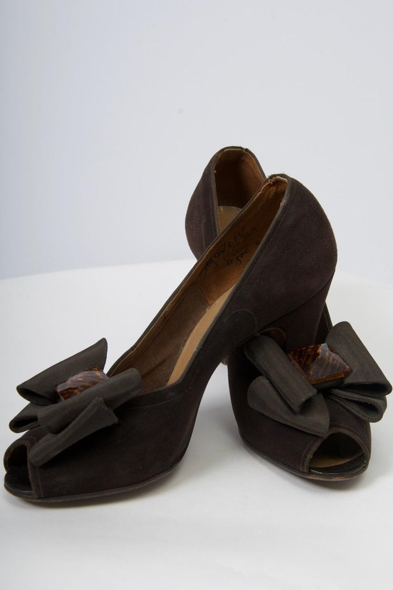 Sophisticated and elegant late 1940s-early 1950s brown suede pumps featuring an open toe, chunky heel, and large grosgrain bow centering a tortoise ornament. Made by Delman for Bergdorf Goodman. From an estate of European royalty. Marked size 6C,