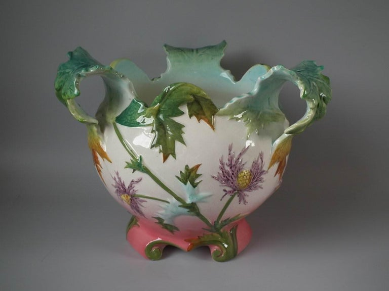Delphin Massier Majolica jardinière which features flowering thistles. Coloration: cream, pink, green, are predominant. The piece bears maker's marks for the Delphin Massier pottery.