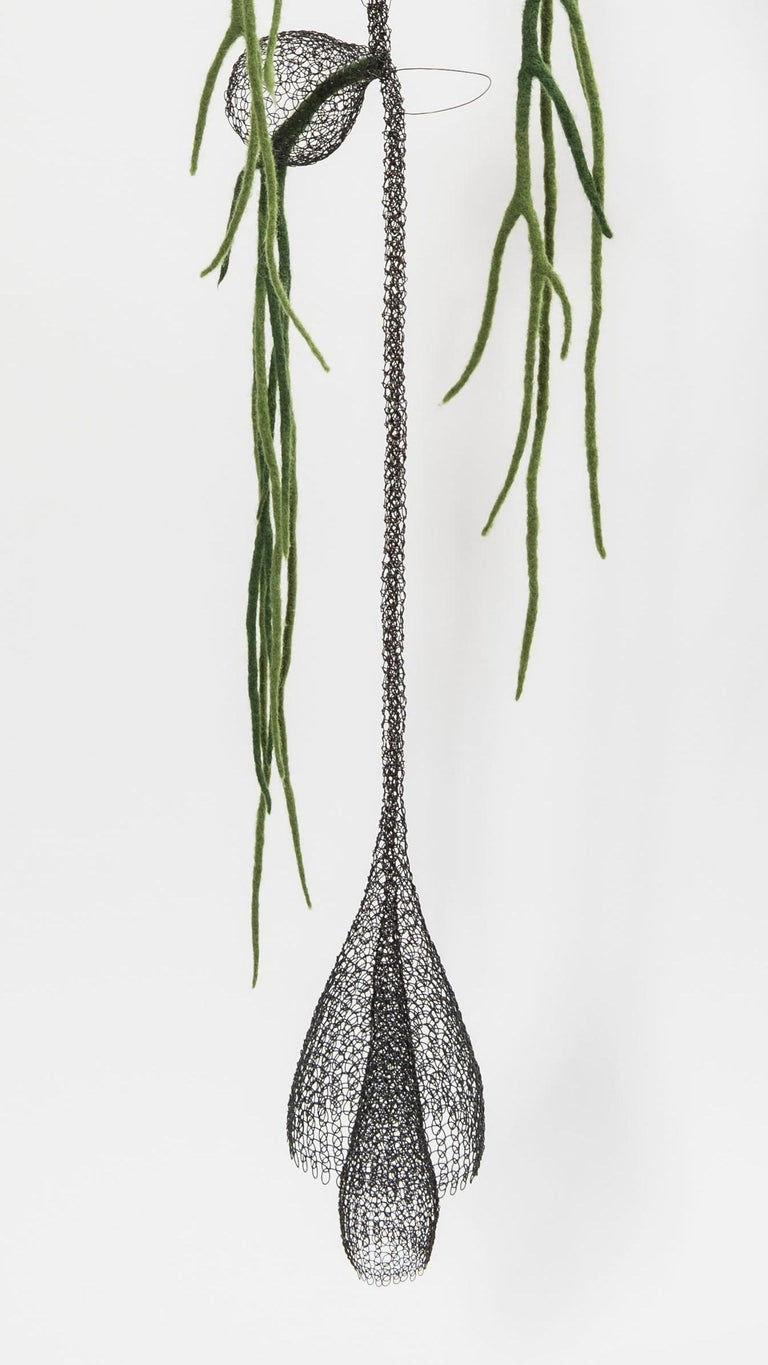 This artwork named «Liane I» is a meshwork combining with felted wool, created and entirely handmade from annealed iron wire and green felting wool by artist Delphine Grandvaux. Inspired by nature and plants, from the most visible to the least