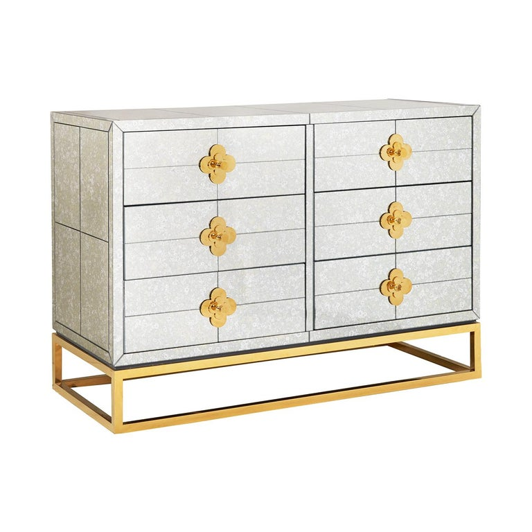 Reflectology. Minimalist forms meet Maximalist glamour. Our Delphine six-drawer dresser features antiqued mirror with a polished brass base and jewel-like quatrefoil escutcheons. Each drawer opens to reveal a bright robin's egg blue interior.