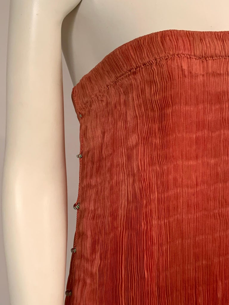 A beautiful shade of coral silk is accented with a braided cord and striped Venetian glass beads on either side> It slips on with an elastic top, or waistband if you prefer to wear it as a skirt. I have photographed it both ways. It is in excellent