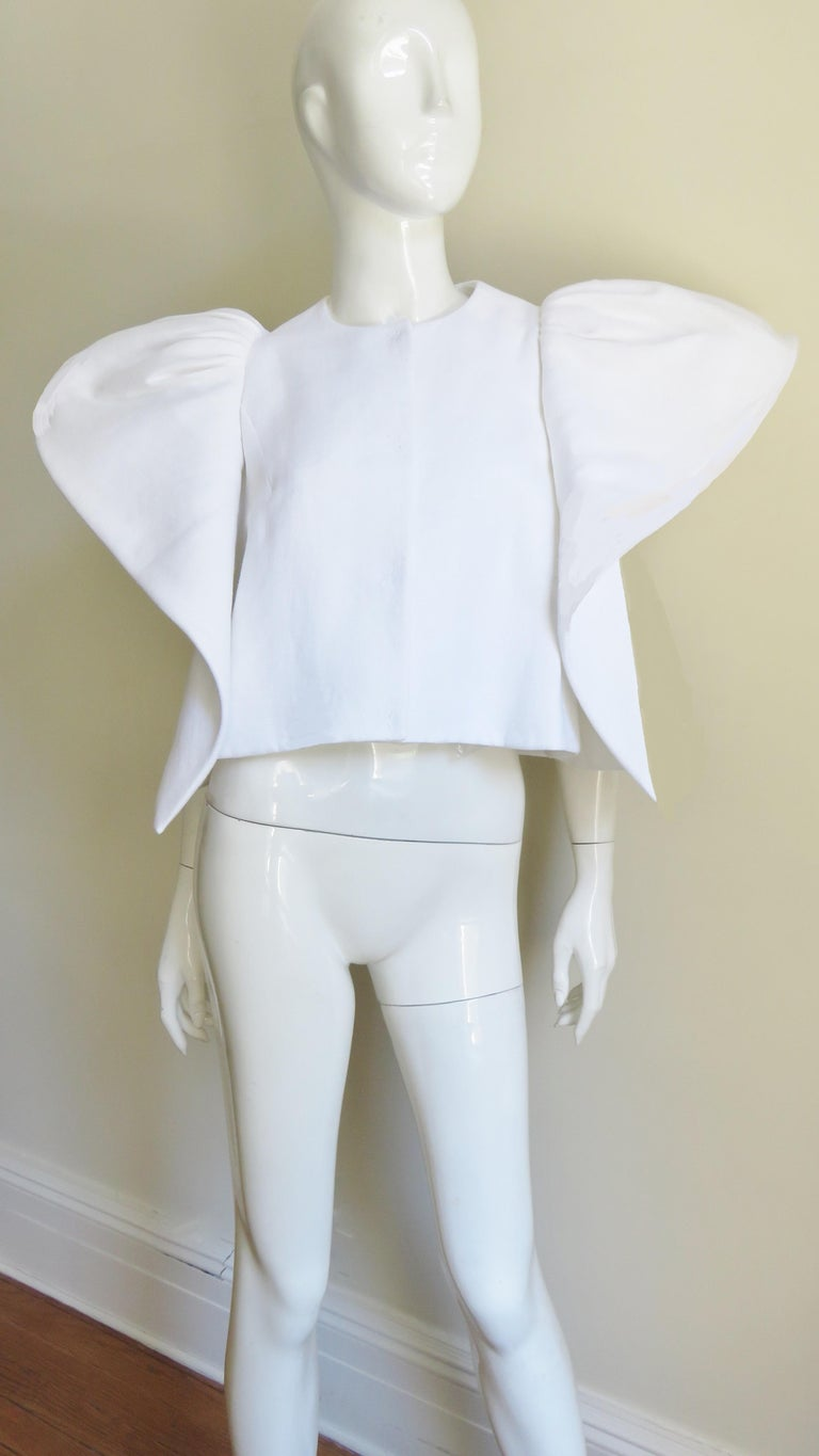 A fabulous sculptural white linen jacket from Deplozo.   It has a large silver dome front closing and fabulous panels encircling the armholes draping to the hem front and back and flaring at the the shoulders.  It is lined in fine white polished