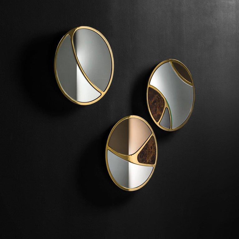 A combination of refined materials in a unique design, this mirror features three sections, elegantly divided by a laser-cut metal frame with a bronze finish: one of Emperador marble, one in smokey gray and the larger section in clear mirror. The