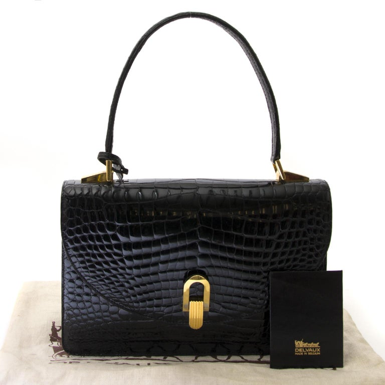 Good preloved condition  Delvaux Black Croco Handbag  This gorgeous handbag by Delvaux is a truely unique designer piece. The bag is crafted in black croco leather and features gold-tone hardware. It opens with a flap and a push button, that gives
