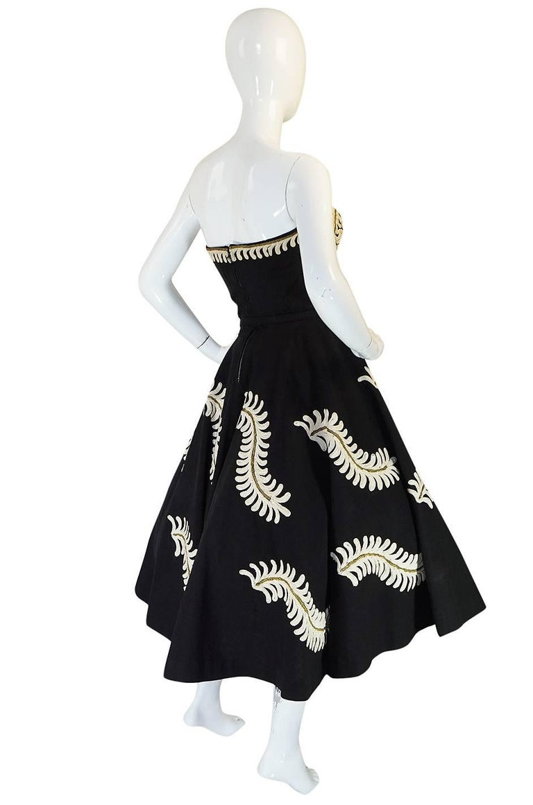 This is a wonderful dress from the fifties that is beautifully feminine. It is also striking and dramatic and has been made by hand. The fabric that it is made from is a heavy silk faille that gives the dress its structure and body. It is