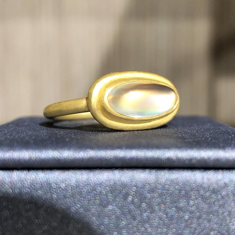 One of a Kind Ring handmade by artisan jeweler Denise Betesh featuring a magnetizing 2.19 carat cabochon-cut oval rainbow moonstone with an unusual orangey-pink phenomena comparable in color to the highly sought-after padparadscha sapphire. The gem