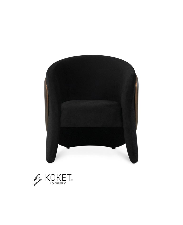 Eye-catching yet with an air of understated class, the slender layered frame of the Denise chair perfectly cups around you while bringing chic style to its surroundings.  Seat upholstery: Smooth velvet color 18 Black from the KOKET TEXTILES