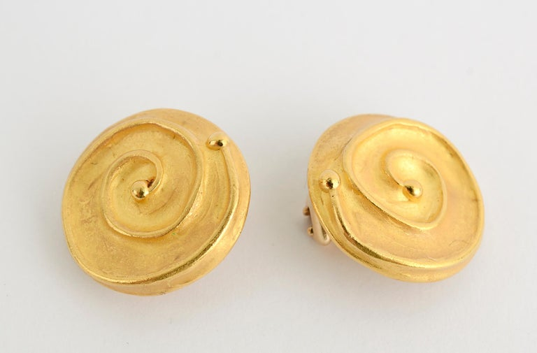 Stylish earrings by Denise Roberge that look simultaneously ancient and modern. An irregular glossy gold coil sits upon a matte finish disc. The back, which would only be seen by the wearer, has yet another texture. Clip backs can be converted to