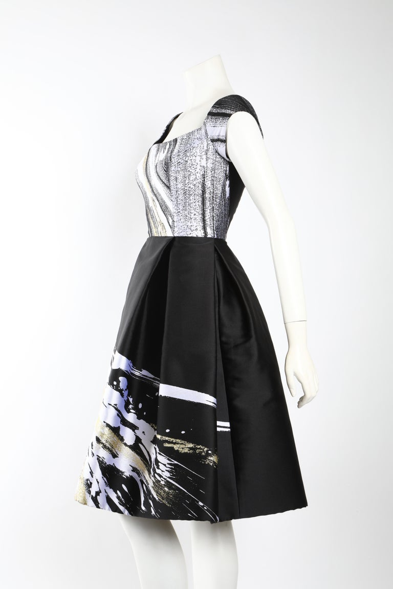 Cocktail dress by Dennis Basso in black and white adorned with a whimsical splash of gold. Features a boat neck and cap sleeves. Fitted through the bodice with a full skirt that hits at the knee. Boning in the bodice creates structured shape, which
