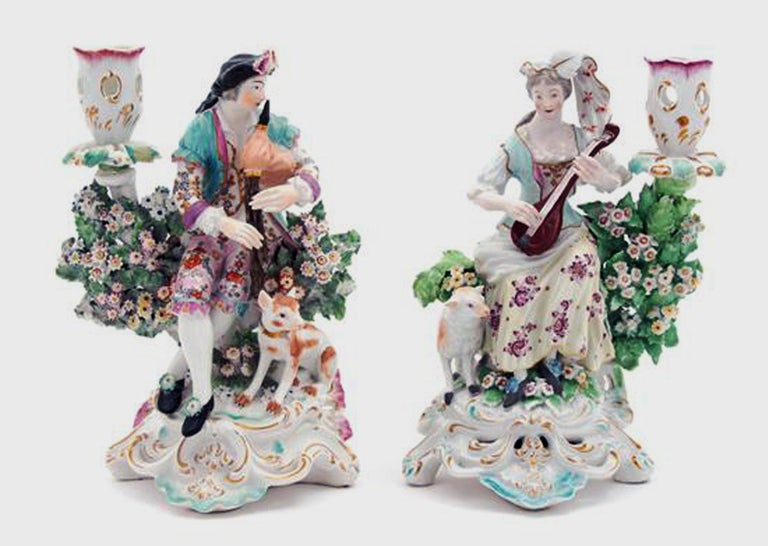 Derby Porcelain candlesticks with figures of musicians,  circa 1760-1765  The pair of Derby Porcelain figures of musicians are on an openwork scroll base, the man is playing the bagpipes with a dog at his feet and the woman plays a lute with a