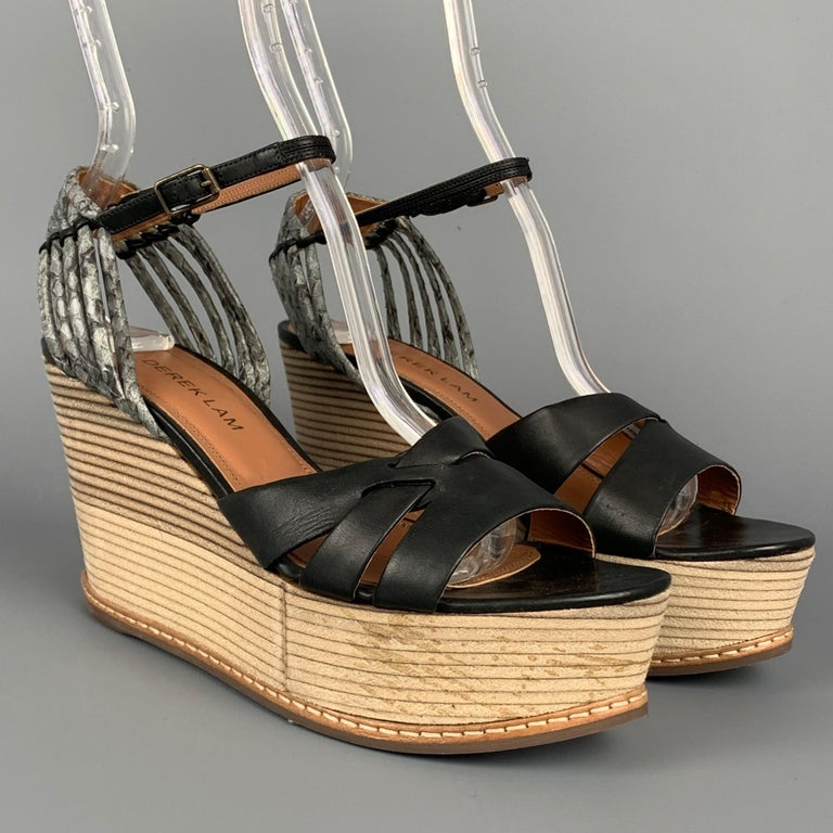 DEREK LAM sandals comes in a black & tan leather featuring a ankle strap and a wooden wedge heel. Made in Italy.  Very Good Pre-Owned Condition. Marked: EU 36  Measurements:  Heel: 3.5 in. Platform: 1.25 in.