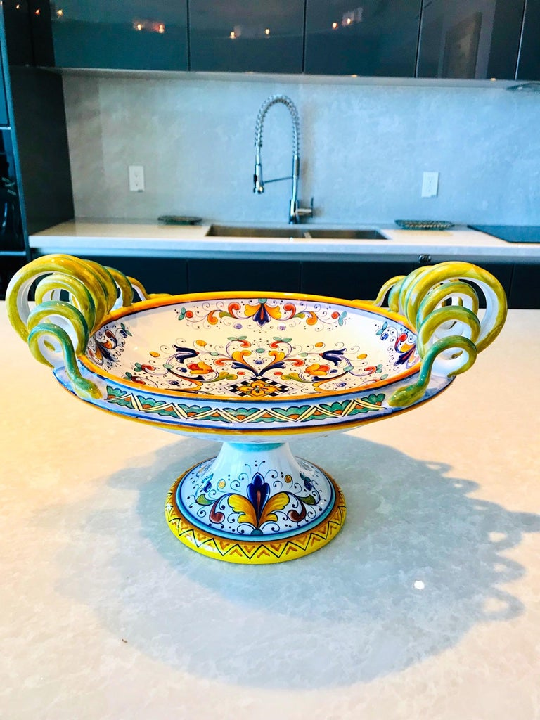 Exquisite Majolica centerpiece bowl with hand painted tin glaze over earthenware pottery. Handmade with pedestal base and stylized serpentine handles and elaborate painted designs throughout. In vibrant hues of yellow, blue, and green over white.
