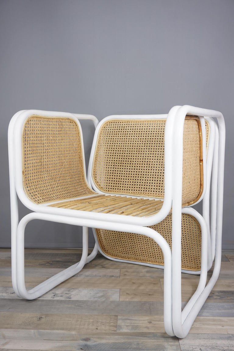 Design and original lounge armchair with white lacquered rattan frame and natural wicker caned, gorgeous and airy structure.